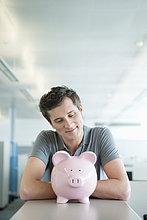 Geschäftsmann schaut auf ein Sparschwein und lächelt