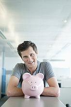 Geschäftsmann lächelt in der Nähe eines Sparschweins