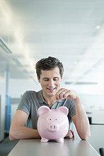 Geschäftsmann beim Einwerfen einer Münze in ein Sparschwein