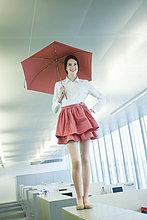 Geschäftsfrau, die einen Schirm hält und auf einem Schreibtisch im Büro steht.