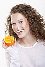 Porträt einer Frau, die eine halbe Orange hält und lacht