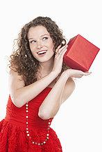 Frau hält ein Geschenk in der Nähe ihres Ohres