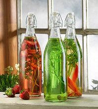 Drei Flaschen eingelegte Kräuter auf der Fensterbank