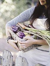 Eine junge Frau in einem Gemüsegarten, die einen Korb mit frisch geerntetem Bio-Gemüse, Paprika und einer Eierpflanze trägt.