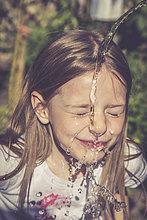 Kleines Mädchen, das sein Gesicht mit einem Wasserstrahl erfrischt.