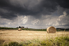 Italien, Toskana, Chianti, toskanische Landschaft mit Heuballen bei aufkommendem Gewitter