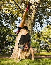 Junge Frau beim Handstand im Park