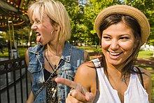 Zwei junge Frauen, die im Park die Zunge zeigen und herausstrecken.