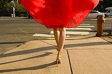 Taille unten Aufnahme einer jungen Frau, die den Bürgersteig entlang schlendert und einen roten Rock trägt.