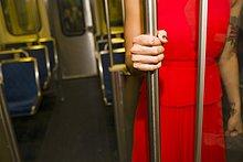 Ausschnitt einer jungen Frau in rotem Kleid in der U-Bahn