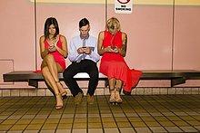 Drei junge erwachsene Freunde texten auf Smartphones, während sie in der U-Bahn-Station sitzen.