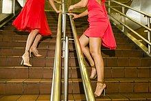 Ausschnitt zweier junger Frauen in roten Kleidern auf der U-Bahn-Treppe
