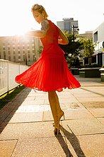 Junge Frau, die im roten Kleid wirbelt