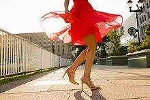 Taille unten Ansicht der jungen Frau, die beim Tragen des roten Kleides wirbelt