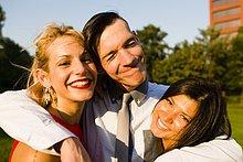 Porträt von drei jungen erwachsenen Freunden beim Umarmen