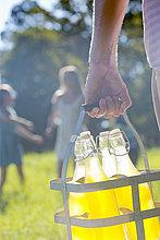 Nahaufnahme eines Mannes, der eine Kiste mit Saftflaschen trägt, mit einer Familie, die in der Ferne spielt.