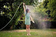 Mädchen kühlt sich mit Gartenschlauch ab
