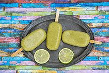 Metalltablett mit Avocado-Eis-Lollies und Limettenscheiben