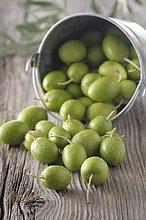 Grüne Oliven auf rustikalem Holzuntergrund