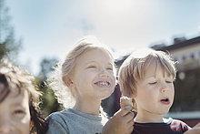 Blick auf Freunde, die an einem sonnigen Tag im Hof Eis essen.