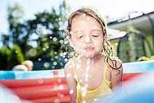 Kleines Mädchen sitzt im Planschbecken und spritzt mit Wasser.