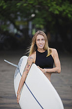 Porträt einer lächelnden Frau mit Surfbrett am Strand