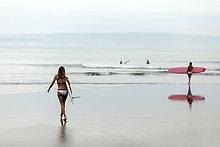 Frau mit Surfbrett am Meer